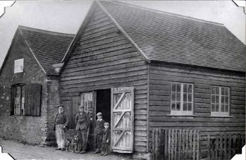 William Prudden and family standing outside the smithy [Z50/21/23]