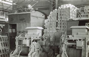 Interior of shed with stacks of bricks, workmen and machinery [Z41/LB10/1/2/29]